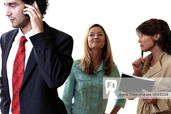 Geschäftsmann auf einem Mobiltelefon mit seinen zwei Sekretären steht hinter ihm sprechen