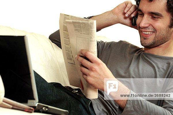 Nahaufnahme eines jungen Mannes eine Zeitung lesen und sprechen auf einem Mobiltelefon