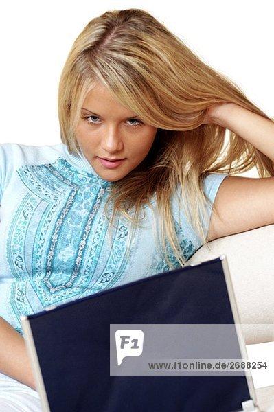 Porträt von geschäftsfrau liegender an einen laptop
