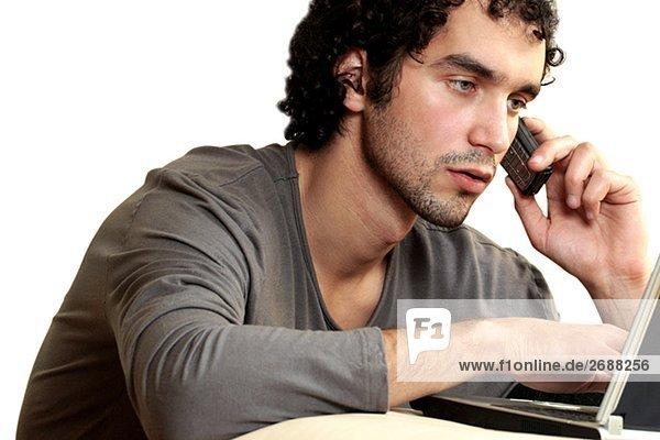 Nahaufnahme eines jungen Mannes reden auf einem Mobiltelefon mit einem laptop