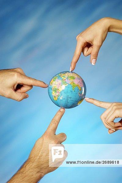 Nahaufnahme eines Mannes und einer Frau Hände auf einem Globus