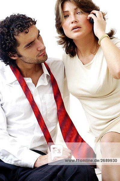Portrait einer jungen Frau Gespräch auf einem Handy mit ein junger Mann sitzt neben ihr