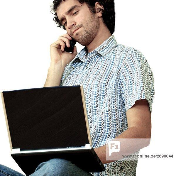 Junger Mann auf einem Mobiltelefon reden und benutze ein laptop