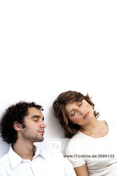 Erhöhte Ansicht eines jungen Paares gegen eine Wand schlafen