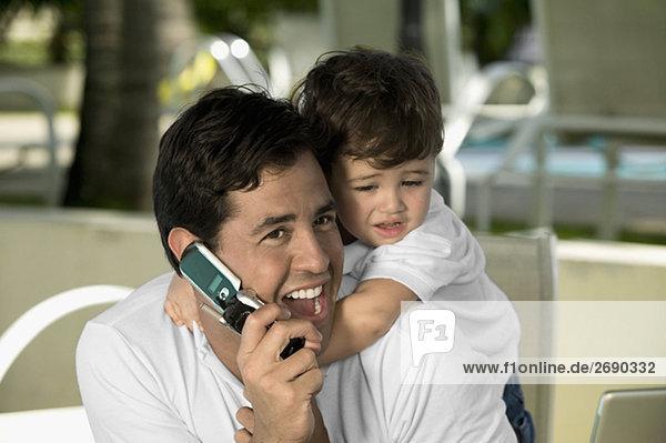 Nahaufnahme eines Vaters sprechen auf einem Mobiltelefon mit seinem Sohn umarmt von hinten
