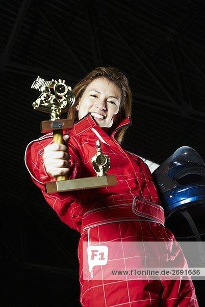 Portrait von einem weiblichen Gokart Racer zeigt ihre Trophy und lächelnd