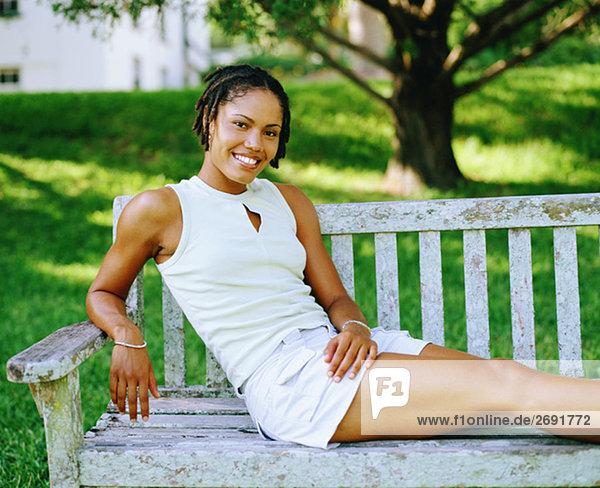 Portrait einer jungen Frau sitzt auf einer Bank und Lächeln  Bermuda