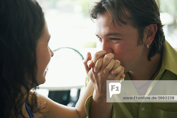 Close-up of a mid adult man kissing a young woman's hand