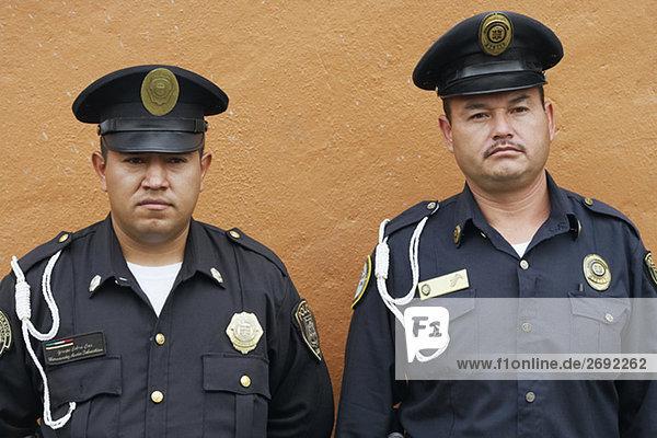 Portrait von zwei Polizisten an einer Wand