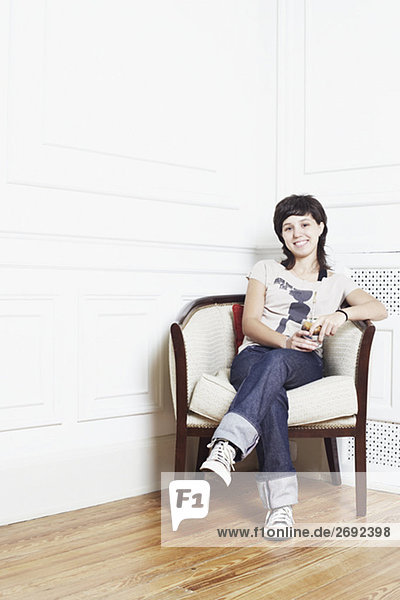 Portrait of a young woman sitting in an armchair and smiling