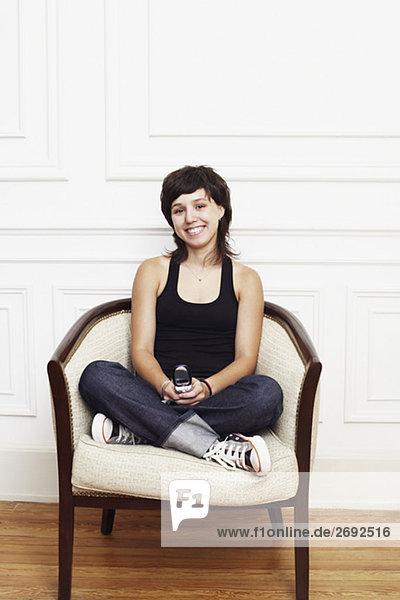 Portrait einer jungen Frau im Sessel sitzen und halten ein Mobiltelefon