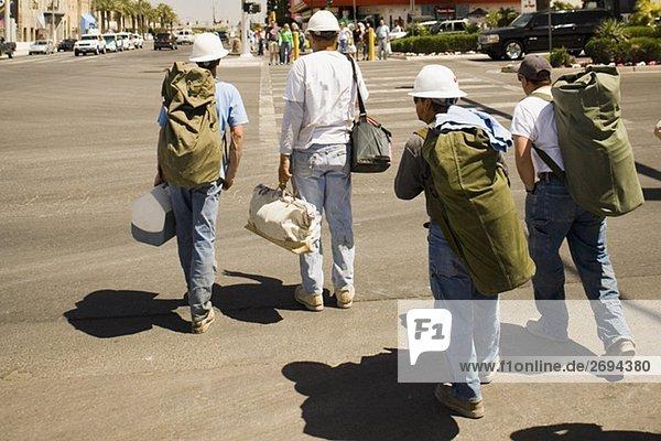 Rückansicht von vier Männern überqueren einer Straße mit Taschen