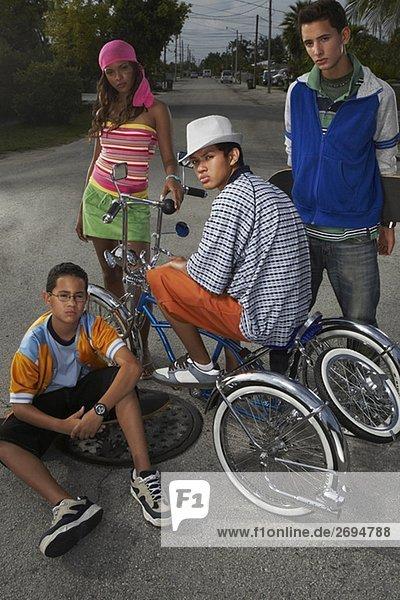 Auf einem low rider Fahrrad mit seinen drei Freunden neben ihm ein Teenager Porträt
