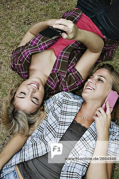 Erhöhte Ansicht der zwei jungen Frauen liegen in einem Park und Mobiltelefone verwenden