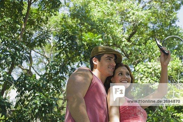 junges Paar ein Foto von sich selbst mit einem Mobiltelefon und lächelnd