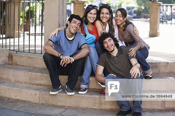 Zwei junge Männer mit drei jungen Frauen auf Schritte sitzen und lächelnd