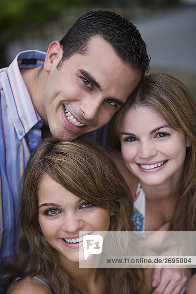 Portrait of a young man smiling with two young women