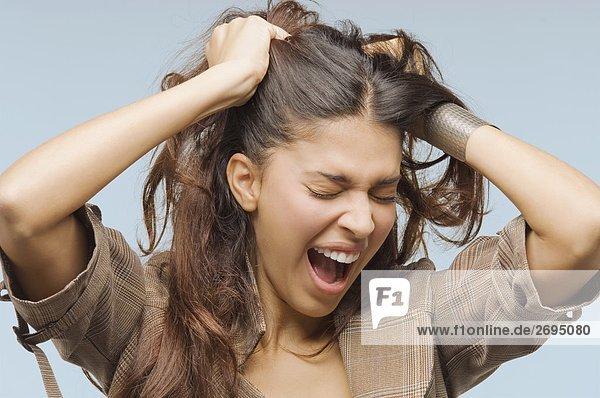 Nahaufnahme einer jungen Frau gellee mit den Händen im Haar