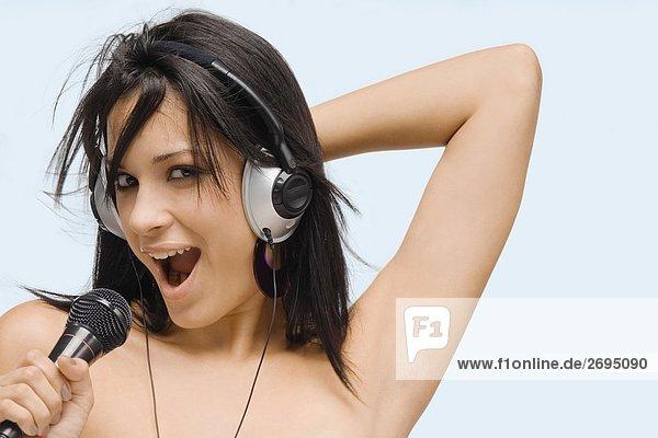 Portrait einer jungen Frau singen in ein Mikrofon