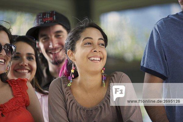 Nahaufnahme von drei jungen Frauen und ein junger Mann lächelnd