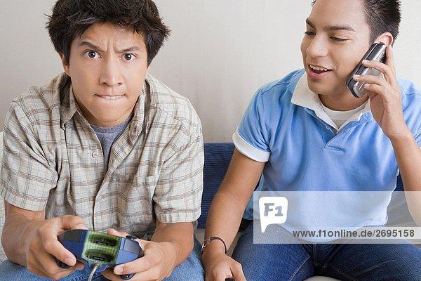 Nahaufnahme eines jungen Mannes Video-Spiel mit einem anderen jungen Mann sprechen auf einem Mobiltelefon neben ihm spielen