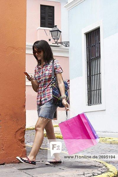 Frau tragen Tragetaschen und mithilfe eines Mobiltelefons  Old San Juan  San Juan  Puerto Rico