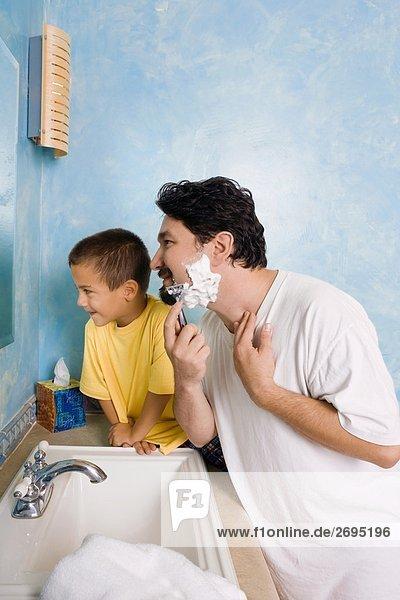 Seitenansicht eines Mitte Erwachsenen Mannes rasieren mit seinem Sohn sitzt neben ihm im Bad