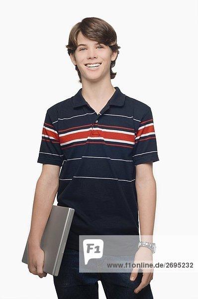 Ein Teenager hält einen Laptop und lächelnd portrait