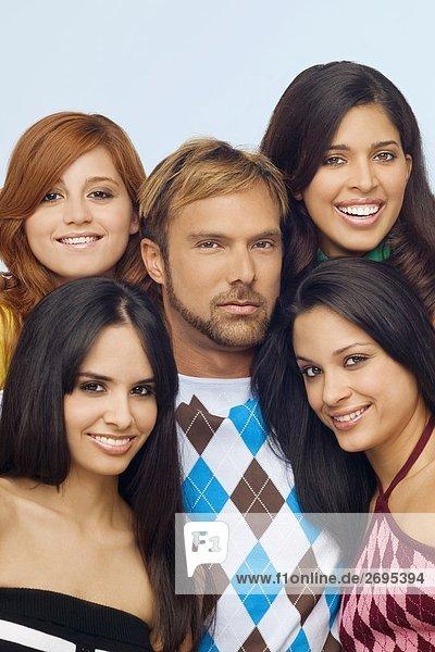 Porträt eines mittleren erwachsenen Mannes posiert mit vier junge Frauen