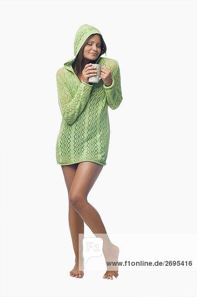 Junge Frau stehend und halten eine Tasse Kaffee