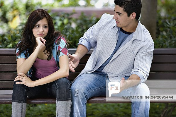 Close-up of a young couple sitting on a park bench