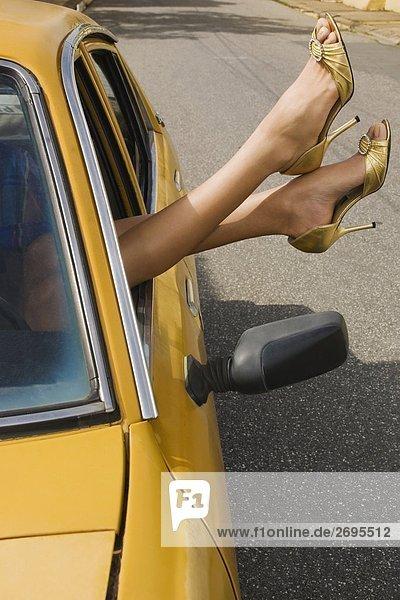 Nahaufnahme of a woman's Beine vor dem Fenster eines Autos