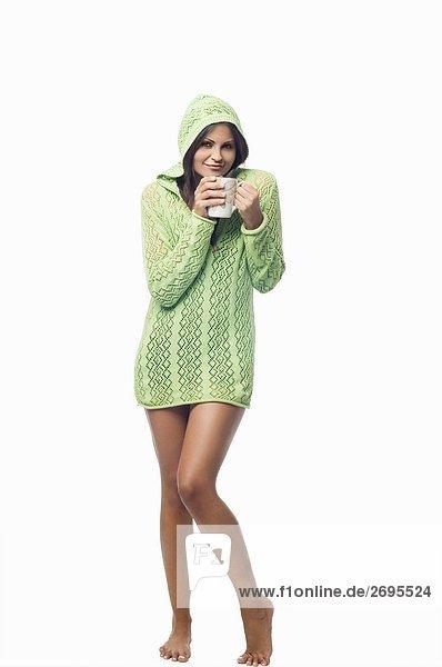 Portrait einer jungen Frau stehend und halten eine Tasse Kaffee