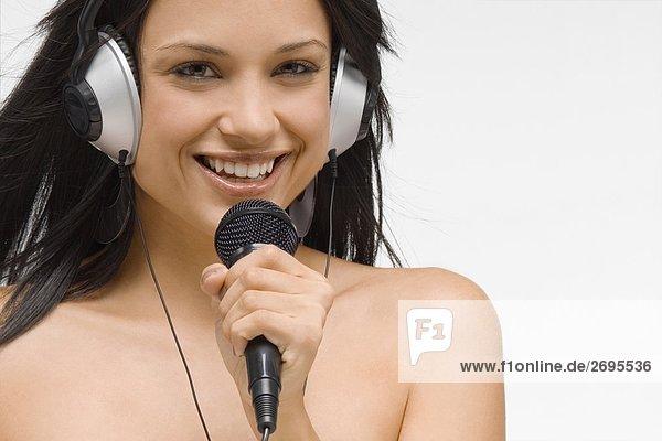 Portrait einer jungen Frau hält ein Mikrofon und lächelnd
