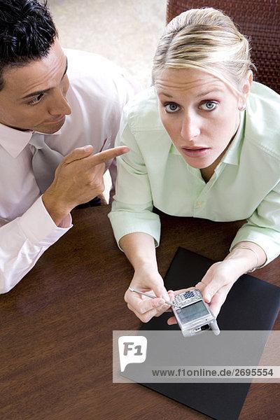 Porträt von geschäftsfrau hält ein Mobiltelefon mit einem Geschäftsmann neben ihr