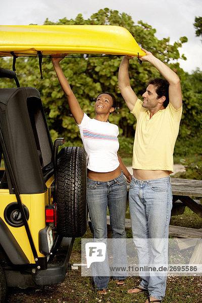 Junge Frau und ein Mitte Erwachsenen Mann laden ein Kajak auf einem jeep