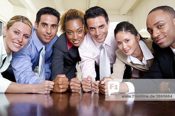 Portrait einer Gruppe von Führungskräften mit ihren Fäusten auf einem Tisch