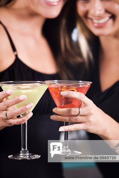 Two young women toasting martinis