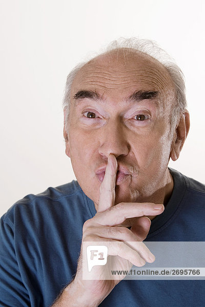 Close-up of a senior man with his finger on his lips