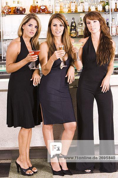 Portrait von drei Frauen halten Gläser in einer bar