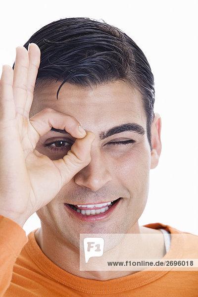 Portrait des eine Mitte erwachsenen Menschen die ein ok Zeichen an seinem Auge