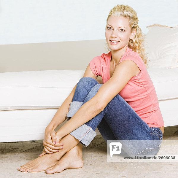 Portrait einer jungen Frau sitzen auf dem Boden