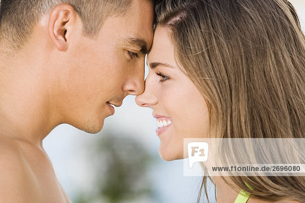 Side profile of a young couple rubbing their noses