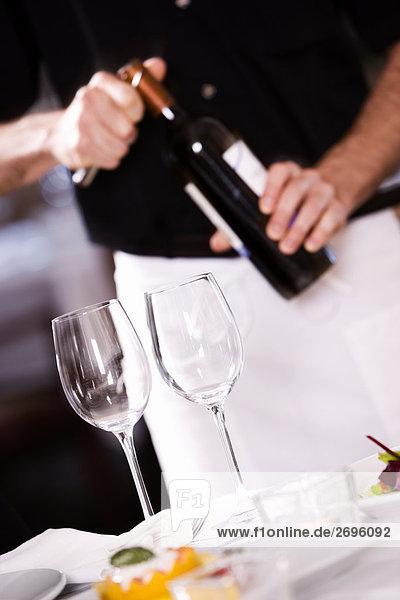 Mitte Schnittansicht eines Mannes öffnen den Korken einer Weinflasche