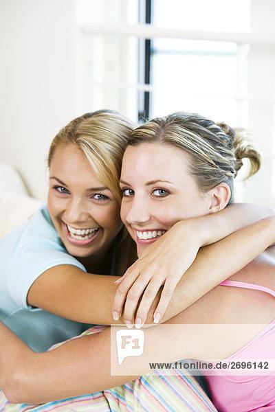 Portrait von zwei jungen Frauen umarmen einander