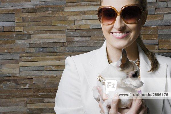 Geschäftsfrau hält ein Welpe und lächelnd