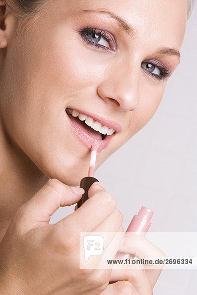junge Frau junge Frauen eincremen verteilen Portrait Lippenstift auftragen