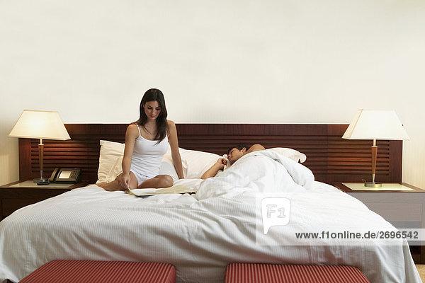 Junge Frau sitzen auf dem Bett mit einem mittleren erwachsenen Mann neben ihr schlafen