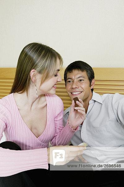 Nahaufnahme einer jungen Frau Fütterung Pralinen mit einem Erwachsenen Mann  Mitte