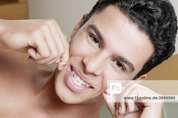 Porträt eines jungen Mannes Zahnseide seine Zähne